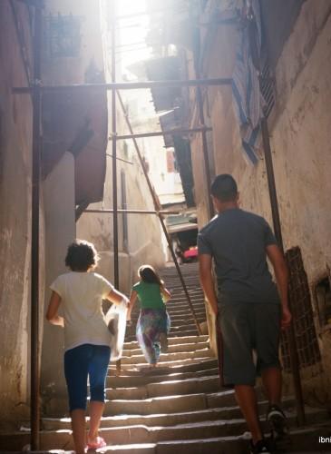 Des enfants montent les escaliers d'un petit chemin de la Casbah