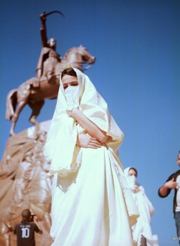 une jeune fille en haïk passe devant la statue de l'Emir Abdelkader, héro national