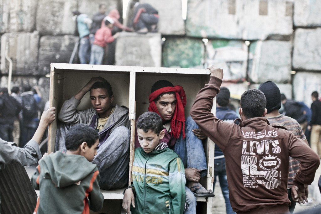Young protestors take shelter behind a barricade during clashes with Egyptian police on the second anniversary of the Revolution. Egypt. Cairo. January 2013 © Moises Saman / Magnum Photos