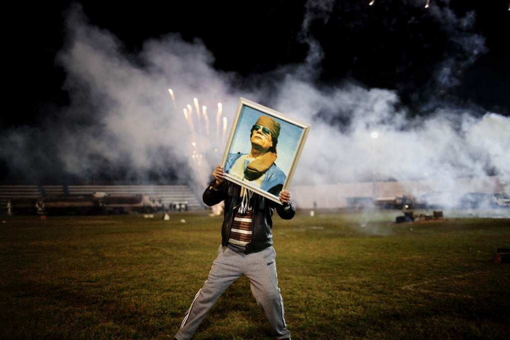 A Quaddafi supporter holds a portrait of the Libyan leader as fireworks go up in the background on a soccer field in a suburb of Zawiyah where government minders took a group of foreign journalists to attend a staged celebration. Libya. March 9, 2011 © Moises Saman / Magnum Photos